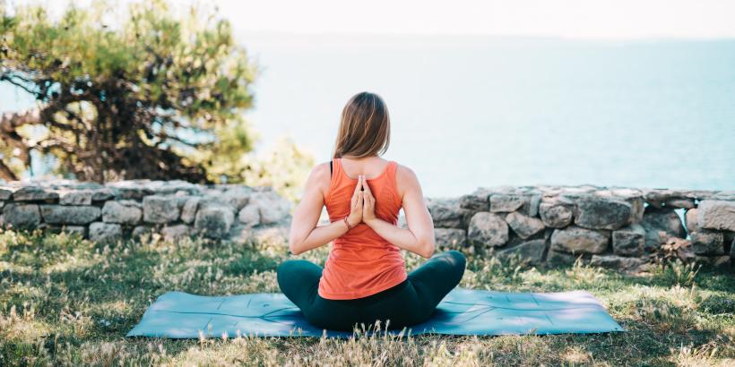 Frau sitzend im Garten beim Yoga in Istrien