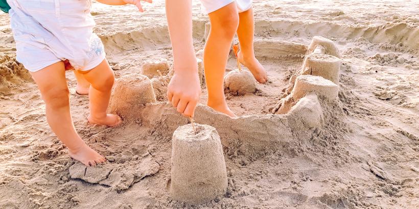 Kinder beim Sandburg bauen