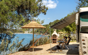 Paar campt mit Wohnmobil direkt am Meer im Lanterna Premium Camping Resort