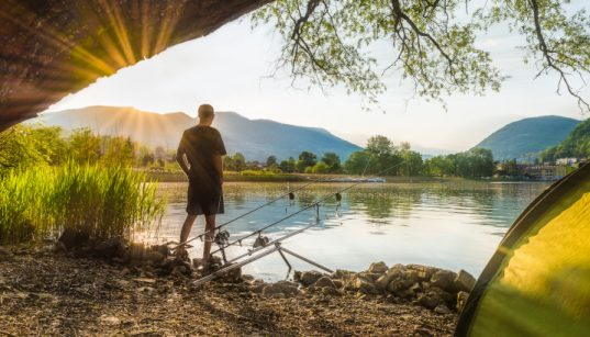 Angler beim Süßwasserangeln am See bei Sonnenuntergang - Angelspot für Süßwasserfische