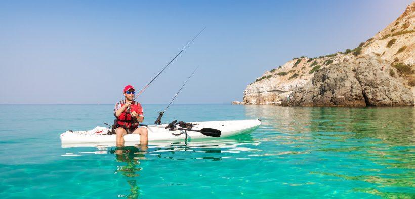 Angler mit eigener Fischfangmethode auf Kajak in türkisem Wasser - Angelmethoden in Kroatien