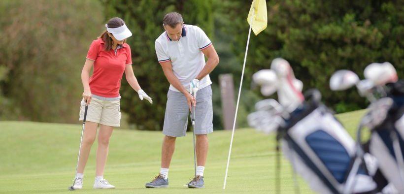 Golfspieler beim Einhalten der Golf Etikette auf dem Green - Verhalten auf dem Golfplatz