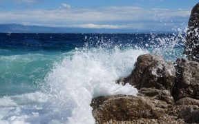Wellen treffen auf Felsen am Kiesstrand bei Wind Oštro ähnlichen Windverhältnissen