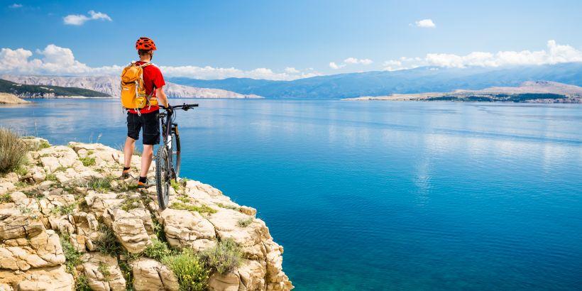 In Kroatien Radfahren am Meer - Biker an einer Klippe an Adria