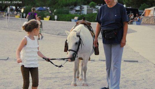 Mädchen hält die Zügel von Pony am Strand beim Ausflug mit Reitzentrum Libertas